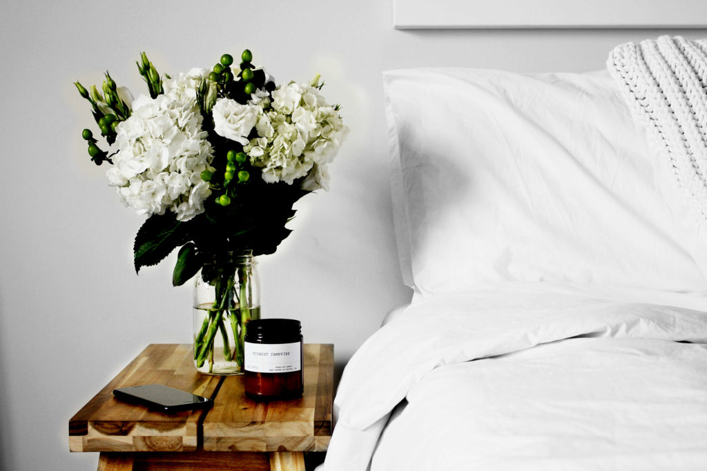 Nightstand with flowers next to bed
