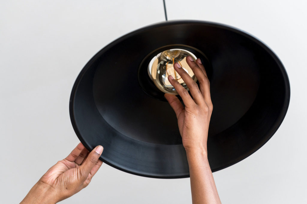 Close up of hand replacing light bulb in a pendant lamp